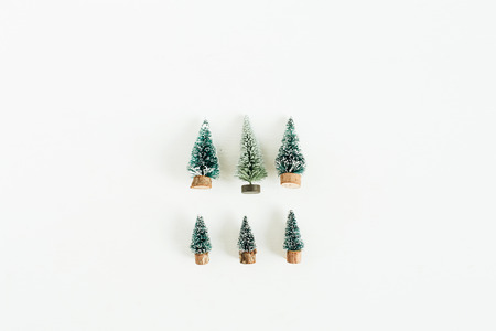 Toy coniferous trees decoration on white background. Flat lay, top view winter, christmas, new year composition.