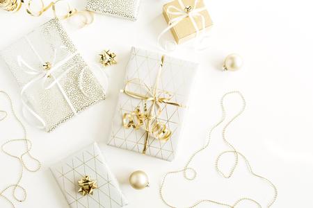 Natale, composizione per le vacanze di Capodanno con scatole regalo dorate, decorazioni su sfondo bianco. Disposizione piatta, vista dall'alto della confezione regalo.