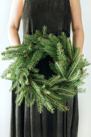 Young woman hold wreath frame made of fir branches. Christmas  New Year composition. Imagens