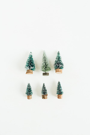 Toy fir-trees decoration on white background. Flat lay, top view winter, christmas, new year composition.