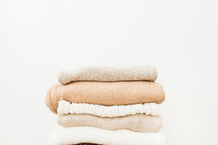 Warm woolen sweaters and pullovers stack on white background. Woman fashion clothes on white background. Stock Photo - 115167831