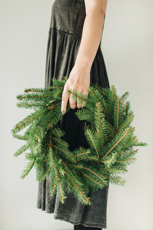 Wreath frame made of fir branches in woman hands on white background. Christmas  New Year composition.
