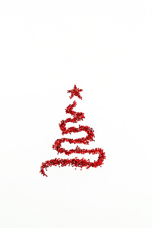 Christmas fir tree symbol made of red glitter sparkles tinsel isolated on white background. Flat lay, top view Christmas, New Year, Winter creative concept.