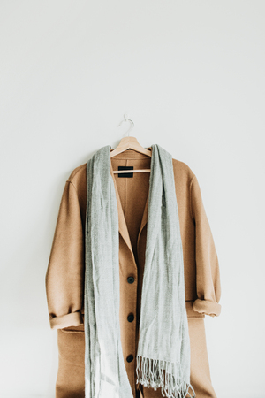 Beige woolen female coat and grey scarf on hanger at white wall. Woman fashion winter cloth concept.