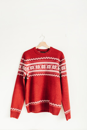 Warm red sweater on hanger on white background. Christmas, New Year, Winter fashion concept.