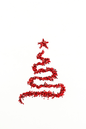 Christmas fir tree shape made of red glitter sparkles isolated on white background. Flat lay, top view Christmas, New Year, Winter creative decoration concept.