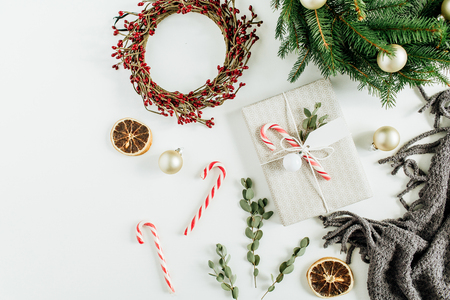 Christmas  New Year composition. Gift box, wreath frames of fir branches and red berries, candies and decorations. Flat lay, top view.