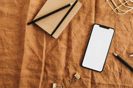 Home office desk workspace with blank screen smart phone on brown blanket. Flat lay, top view minimal blog hero header.
