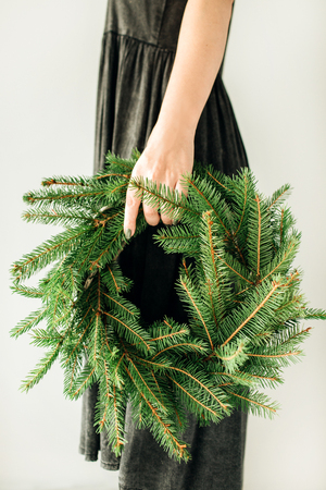 Young woman hold wreath frame made of fir branches. Christmas / New Year composition. Imagens - 115187057