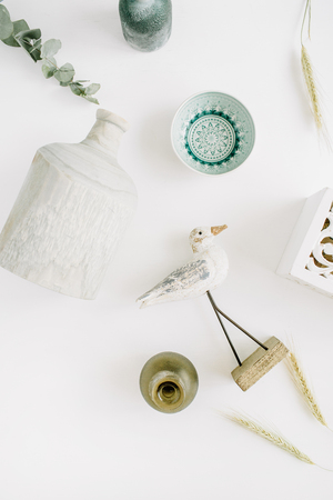 Trendy modern interior decorations. Bird, plate, candlestick, vase. Flat lay, top view background.