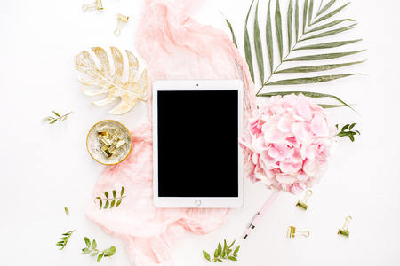 Blank screen tablet, pink hydrangea flowers bouquet, tropical palm leaf, pastel blanket, monstera leaf plate and accessories on white background. Flat lay, top view rose gold home office desk workspac 스톡 콘텐츠