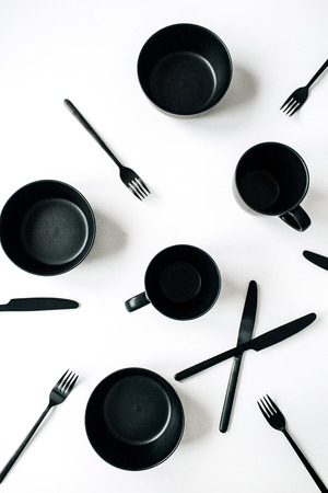 Black trendy kitchenware: forks, knifes, mugs, bowls on white background. Flat lay, top view modern kitchen minimal concept.