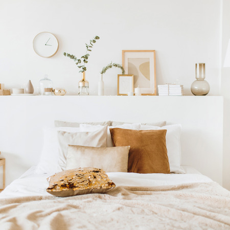 Modern interior design concept. Bright beige and golden style bedroom with bed, pillows, bedcover, clock, eucalyptus branch, vase, candle. 免版税图像