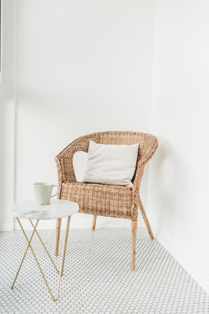 Rattan chair with pillow and marble coffee table at loggia with mosaic floor. Minimal modern Scandinavian nordic interior design concept. Archivio Fotografico - 121432814