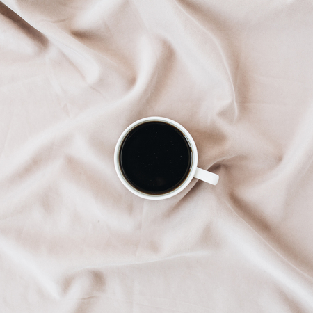 Coffee mug on silk pink blanket. Minimal flat lay, top view background. Banco de Imagens