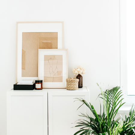 Modern minimal Scandinavian nordic interior design. Chest of drawers, photo frames, palm home plant and decor.