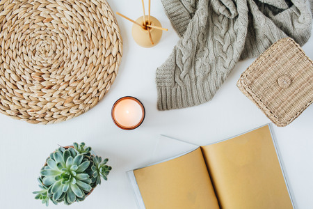 Boho style modern minimal home workspace desk with notebook, succulent, knitted plaid, candle, aroma sticks, straw wicker napkins on white background. Flat lay, top view bohemian lifestyle blog hero header.