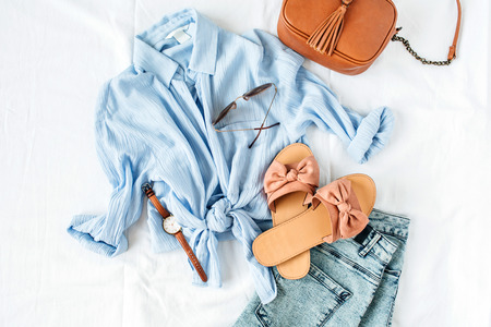 Feminine summer fashion composition with blouse, slippers, purse, sunglasses, watch, jean shorts on white background. Flat lay, top view minimalist clothes collage. Female fashion blog, social media, website concept.