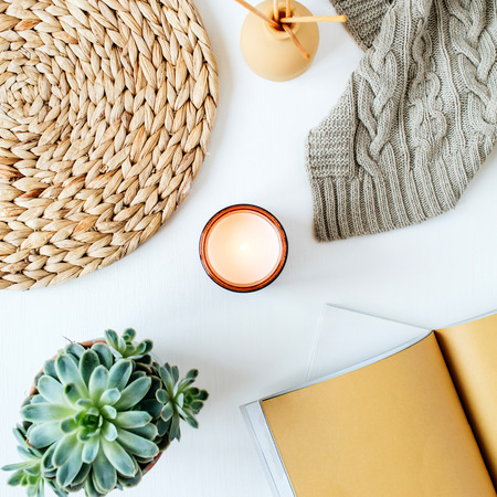 Boho style modern minimal home workspace desk with notebook, succulent, knitted plaid, candle, aroma sticks, straw wicker napkins on white background. Flat lay, top view bohemian lifestyle blog concept.