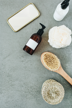 Bath products: liquid soap, brush, mirror, sponge on stone background. Spa concept. Flat lay, top view.