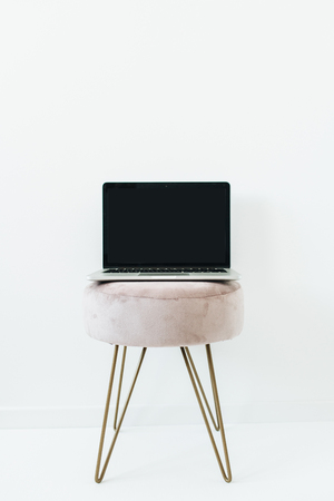 Front view of blank mockup screen laptop on stylish stool on white background. Blog, website, social media hero header. 写真素材