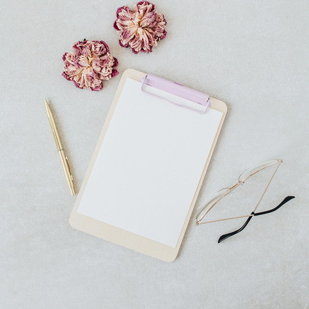 Clipboard mockup. Minimal home office desk with dry peonies, glasses, pen. Flat lay, top view blog template. Banco de Imagens