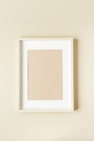 Minimal photo frame on beige wall. Modern interior design concept. Blank copy space mock up.