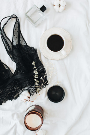 Fashion trendy underwear composition. Bra, perfume, coffee, cotton on white linen. Flat lay, top view beauty blog minimal concept.