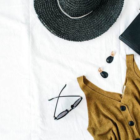 Feminine fashion composition with hat, blouse, earrings, purse, sunglasses on white background. Flat lay, top view minimalist stylish trendy elegant clothes hero header. Stock Photo