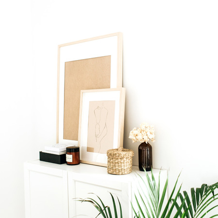 Modern minimal Scandinavian nordic interior design. Chest of drawers, photo frames, palm and decorations.