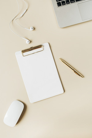 Minimalist home office desk workspace with clipboard, laptop, headphones on beige background. Flat lay, top view modern lifestyle copy space blank mockup.