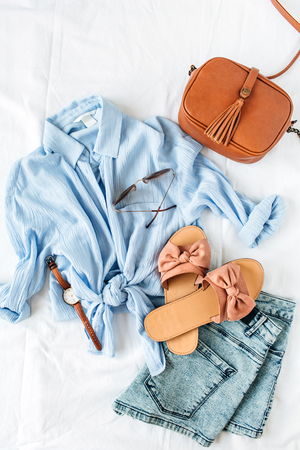 Feminine summer beach fashion composition with blouse, slippers, purse, sunglasses, watch, jean shorts on white background. Flat lay, top view minimalist clothes collage.