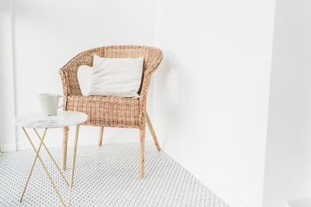 Rattan chair with pillow and marble coffee table at loggia with mosaic floor. Minimal modern Scandinavian nordic interior design concept.
