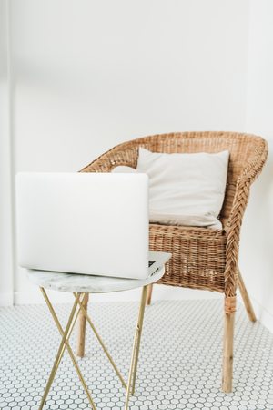 Work at home concept with laptop, rattan chair with pillow and marble coffee table at balcony with mosaic floor. Minimal modern Scandinavian nordic interior design. girl boss blog concept. Stock Photo