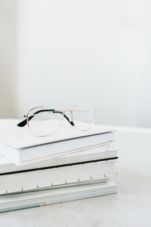 Glasses on books stack. Home office desk concept. Banco de Imagens