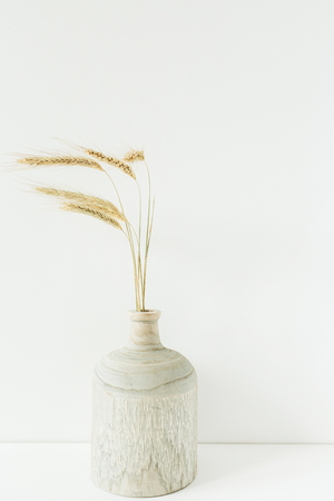 Wheat spikes bouquet in wooden vase on white background.