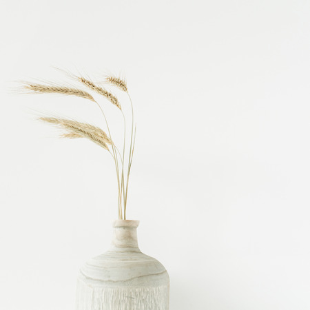 Bouquet d'épis de blé dans un vase en bois sur fond blanc. Banque d'images