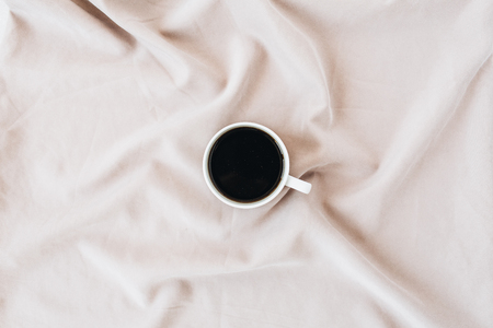 Flatlay of black coffee mug on pastel pink blanket. Minimal top view hero header. Stock Photo