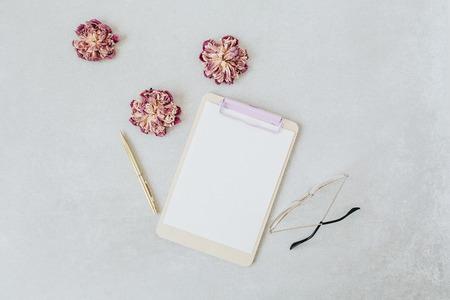 Clipboard mockup. Minimal home office desk with dry peonies, glasses, pen. Flat lay, top view social media hero header.