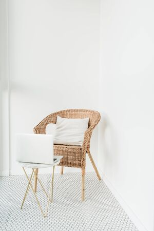 Rattan chair with pillow and marble coffee table at balcony with mosaic floor. Minimal modern bright Scandinavian nordic interior design. Working at home concept with laptop.