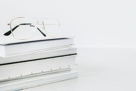 Glasses on books stack. Minimalist business hero header background. Banco de Imagens