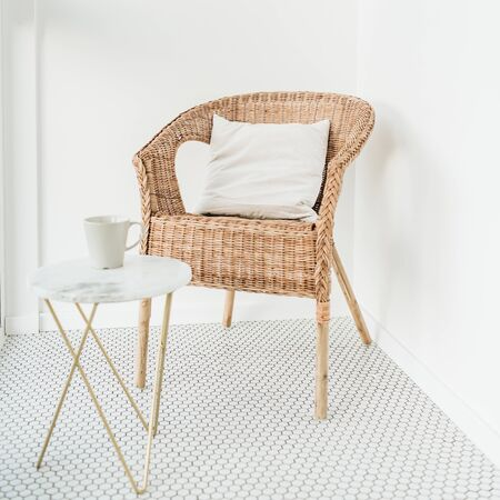 Rattan chair with pillow and marble coffee table at balcony with mosaic floor. Minimal modern bright Scandinavian nordic interior design concept. Stock Photo