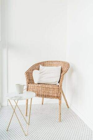 Rattan chair with pillow and marble coffee table at balcony with mosaic floor. Minimal modern bright Scandinavian nordic interior design concept. Archivio Fotografico - 125599770