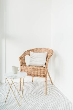 Rattan chair with pillow and marble coffee table at balcony with mosaic floor. Minimal modern bright Scandinavian nordic interior design.