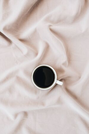 Flatlay of black coffee mug on pastel pink blanket. Minimal top view template. Banco de Imagens