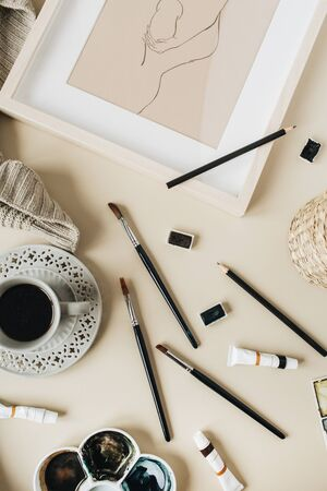 Watercolor artist home office desk workspace on beige background. Coffee cup, paint brushes, painting, watercolor. Flat lay, top view blog, social media, website concept. 스톡 콘텐츠