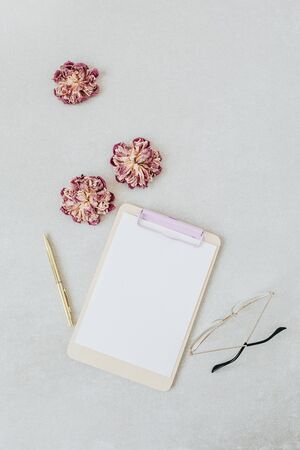Clipboard mockup. Minimal home office desk with dry peonies, glasses, pen. Flat lay, top view blog template. Stock Photo