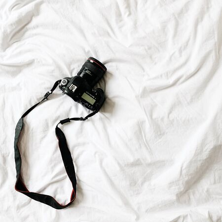 A black camera lying at bed with whit linen. Minimal background. Business , photography concept.