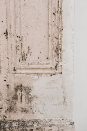 An old shabby pale pink and white door. Vintage and retro concept. Neutral background.