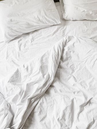 Flat lay, top view of white linen with sheet, blanket and two pillows. Minimal bed concept. Stock Photo